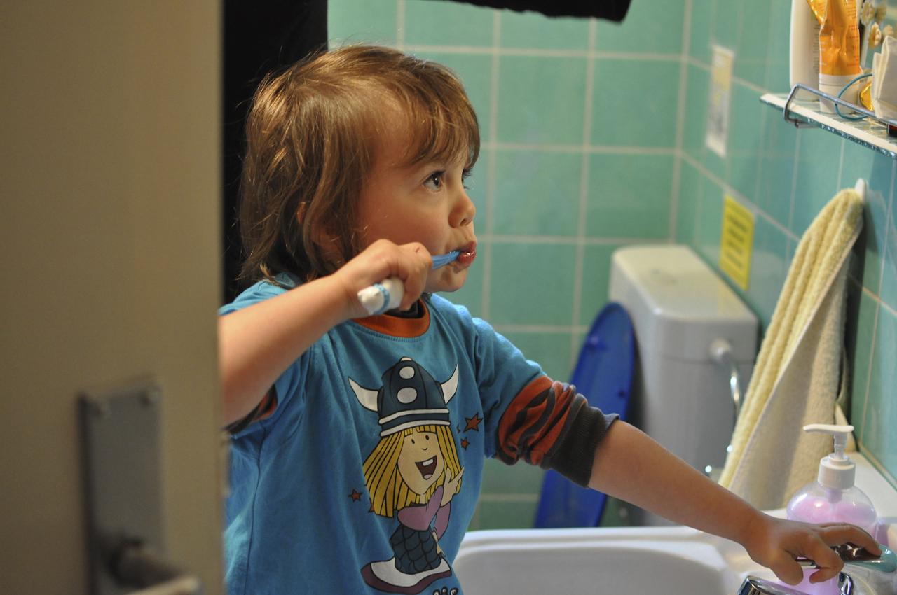 Michael steht im Bad vor dem Waschbecken und putzt sich die Zähne. Michael wohnt mit seiner Schwester und seinen Eltern in Bayern in Garching an der Alz.
