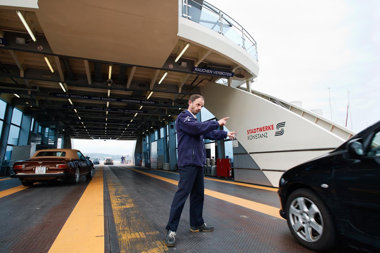 """Schiffsführer Martin Kreissler betätigt sich hier als """"Einweiser"""". Damit auch fur große Lastwagen noch Platz auf der Fähre ist, werden die Pkw nach einem ausgeklügelten System geparkt. Nicht  jeder Kraftfahrer ist mit der ihm zugewiesenen Reihe einverstanden. Dann muss Kreissler seiner Autorität unmissverständlich Nachdruck verleihen."""