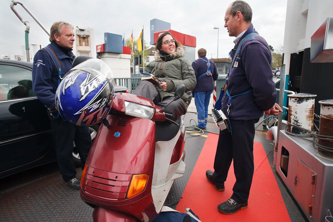 Eine Studentin der Universität Konstanz macht es sich für die Überfahrt auf ihrem Motorroller bequem. Für die beiden Kassierer Meinrad Rembold (r.) und Martin Steiner eine willkommene Abwechslung.