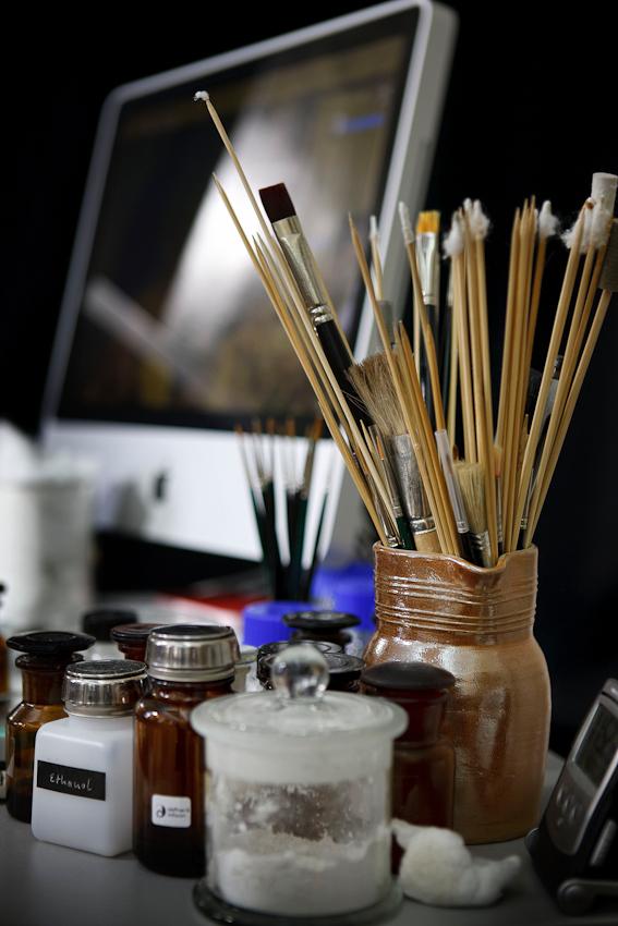 Pinsel, Tupfer und Materialien der Restauratoren vor einem iMac.