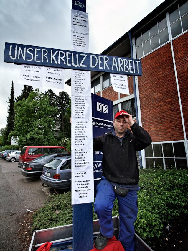 """""""Vor zwei Monaten bin ich aus der katholischen Kirche ausgetreten, jetzt hat mir der Herrgott ein Kreuz geschickt!"""": Oliver Saunus, 43, Monteur bei KBA mit """"seinem"""" Kreuz der Arbeit. Er baut es morgens auf und versteckt es in der Nacht, damit es von der Firmenleitung - wie bei anderen Firmen schon geschehen - nicht nachts entfernt werden kann."""