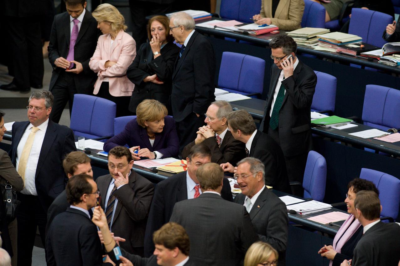 """07 MAI 2010, BERLIN/GERMANY: Bundeskanzlerin Angela Merkel (Mi-L) (CDU), Bundesfinanzminister Wolfgang Schäuble (M) (CDU) und Bundesaußenminister Guido Westerwelle (MI-R) (FDP), während der namentlichen Abstimmungen nach der Bundestagsdebatte zur sog. Griechenlandhilfe, laut Tagesordnung """"Übernahme von Gewährleistungen zum Erhalt der für die Finanzstabilität in der Währungsunion erforderlichen Zahlungsfähigkeit der Hellenischen Republik (Währungsunion-Finanzstabilitätsgesetz - WFStG)"""", Plenum, Deutscher Bundestag"""