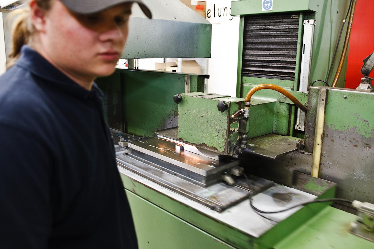 Manuel Schwald, Mitarbeiter der Firma Color Metal, steht an einem halbautomatischen Schleiftisch in der Werkshalle der Firma und bearbeitet einen auf einem Magnetsockel befestigten Metallblock bevor er zur weiteren Verarbeitung in eine CNC-Fräse kommt. Heitersheim im Markgräflerland am 7. Mai 2010 um 11:14.