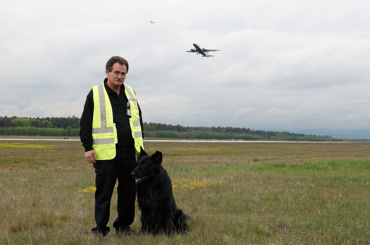 Ein Hundeführer der Airport Security posiert mit seinem schwarzen Deutschen Schäferhund an der Startbahn West vor einem im Hintergrund abhebenden Flugzeug.