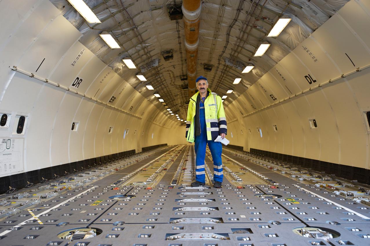 Der Belader im noch leeren Frachtraum eines McDonnell MD-11 Freighters. Sobald die Lufthansa-Maschine am Boden steht, werden die anfallenden Arbeiten von Mitarbeitern der Fraport AG übernommen. Der Frankfurter Flughafen ist mit 71.000 Beschäftigten (2009) die größte Arbeitsstätte Deutschlands.