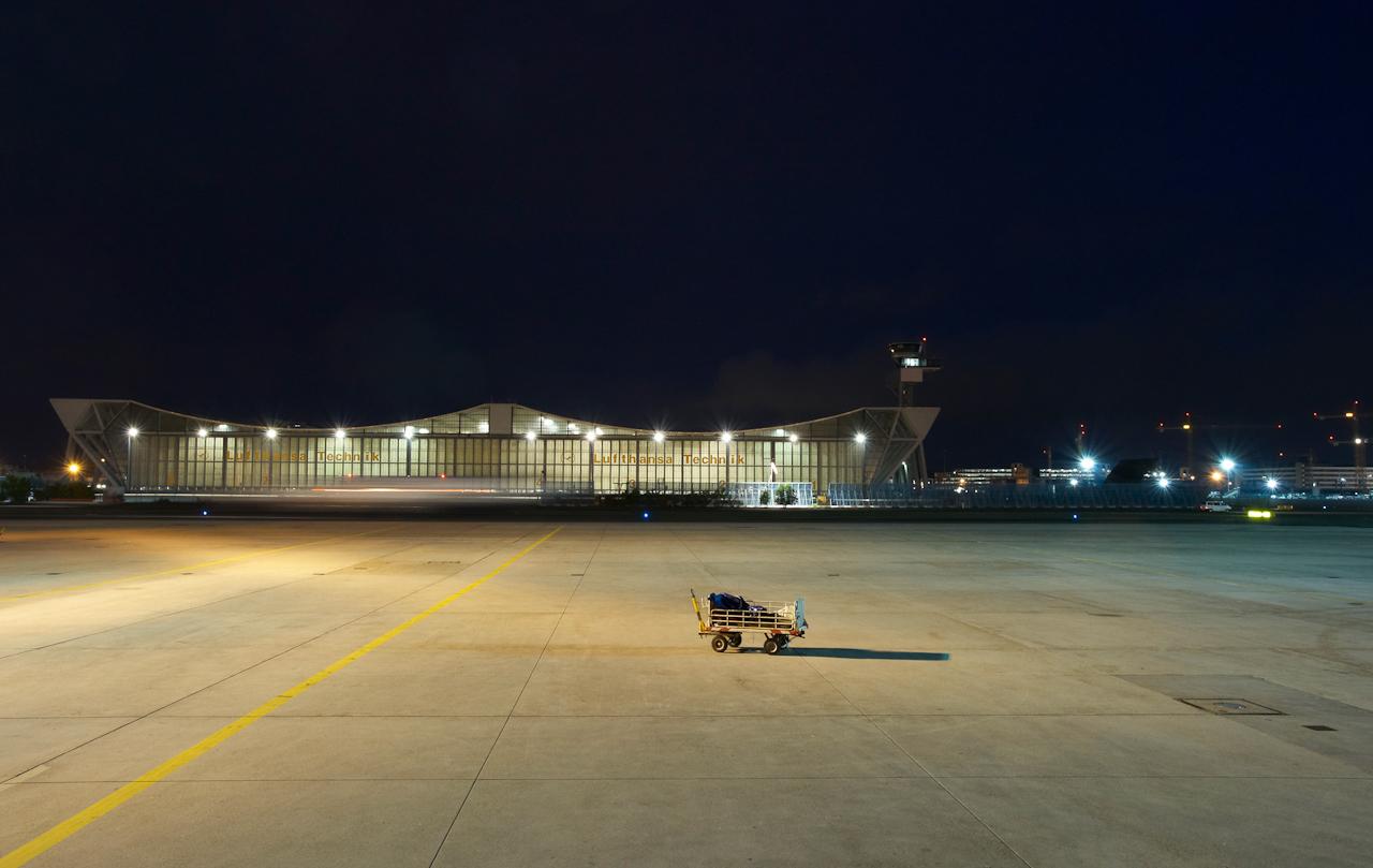 Vor der erleuchtetn Wartungshalle V steht ein verlassener Gepäckwagen einsam am nächtlichen Rollfeld.