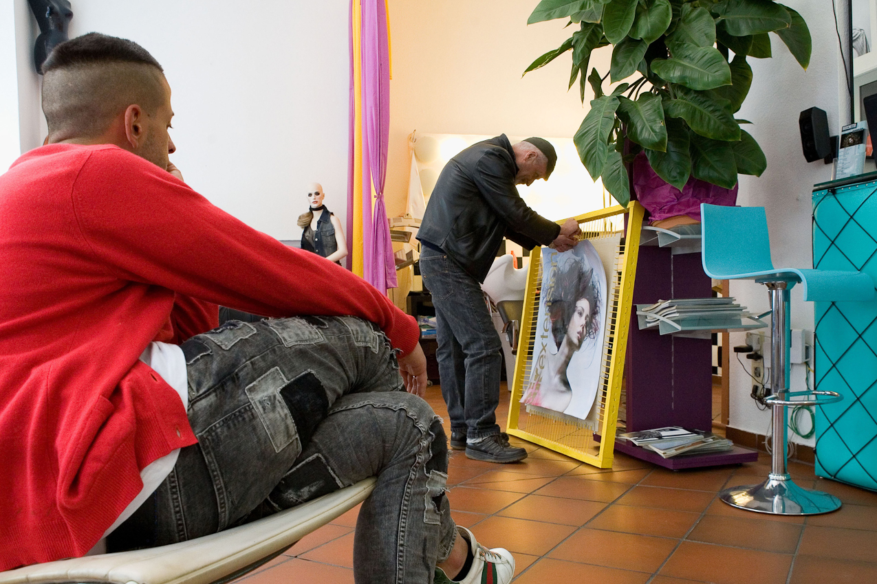 Der Friseur Ciro Boschetto montiert ein Poster für die Dekoration in seinem Geschäft. Sein Assistent Andrea Acciarino sieht zu.