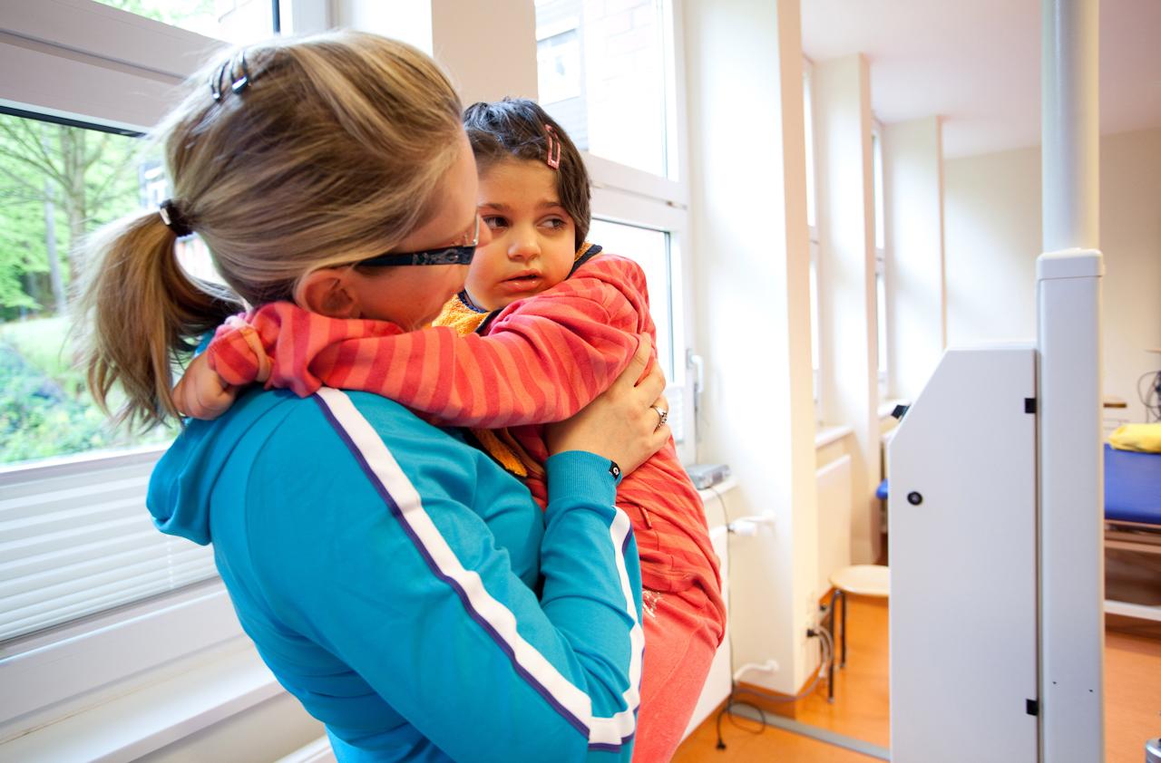 Milena mit ihrer Mama nach den Übungen auf dem Gangroboter. Diese Übungen sind sehr anstrengend und Milena ist etwas ausgepowert.