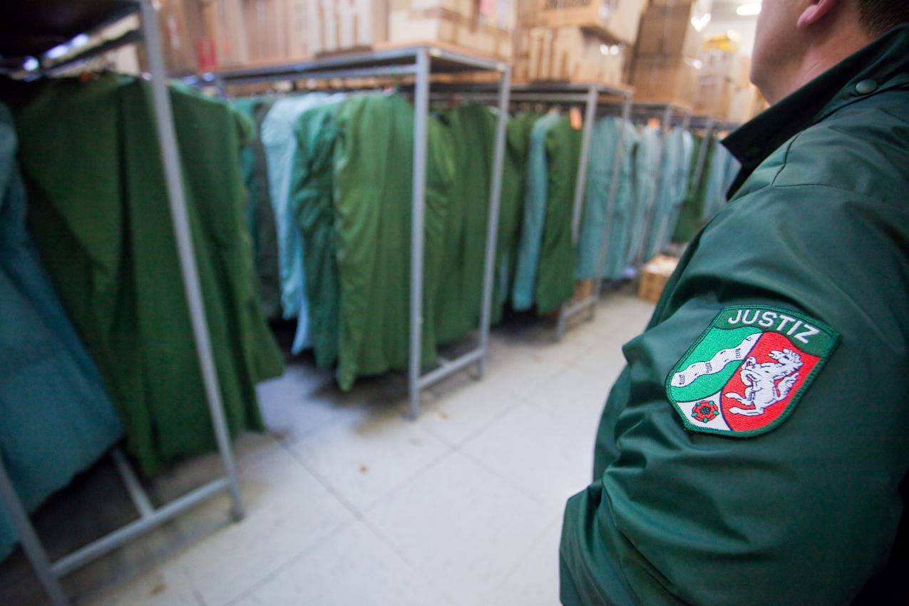 Warten auf die Haftentlassung - Justizbeamter im Lager der Kleidersäcke mit der privaten Kleidung der Gefangenen.