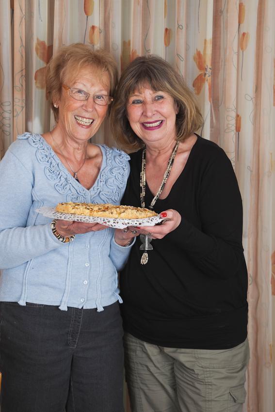 Die langjährige Freundin Ursula Bosking (rechts) gratuliert Gisela Wojciech (links) zum Namenstag und überreicht einen selbstgebackenen Kuchen an Gisela.