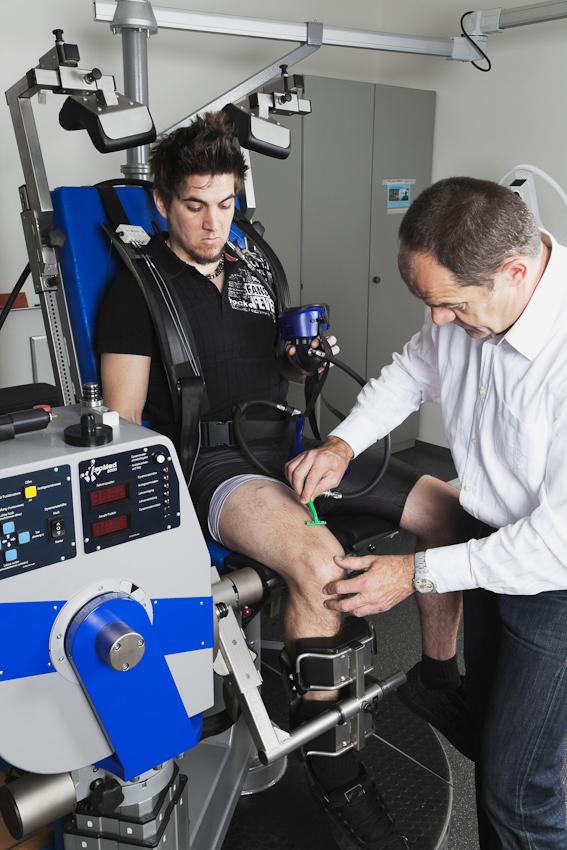 Der Proband Fabian Schurg (links) sitzt auf einer elektronisch gesteuerten Kraftmaschine. Er hält eine Atemmaske in der Hand, die ihn beim Experiment mit sauerstoffarmer Atemluft versorgen soll. Der Laborleiter Dr. Axel Knicker (rechts im Bild) bereitet die Haut über den Oberschenkelmuskeln für die Elektroden vor, die die Muskelaktivität aufzeichnen werden.