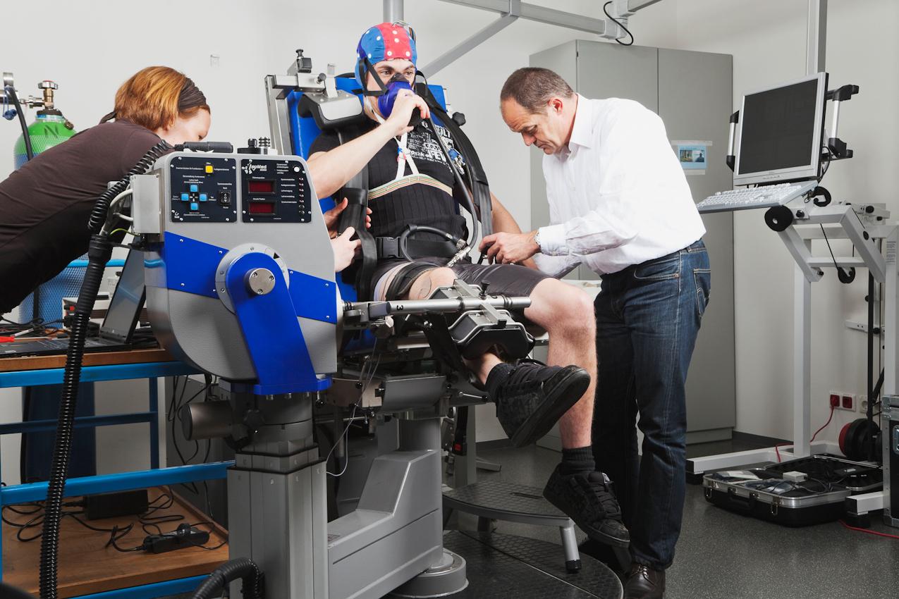 Proband Fabian Schurg (Bildmitte) sitzt auf einer elektronisch gesteuerten Kraftmaschine. Er trägt eine EEG-Kappe und eine Atemmaske. Die Wissenschaftlerin Vera Brummer (links im Bild) und der Laborleiter Dr. Axel Knicker (rechts im Bild) treffen die letzten Vorbereitungen für die Messungen.