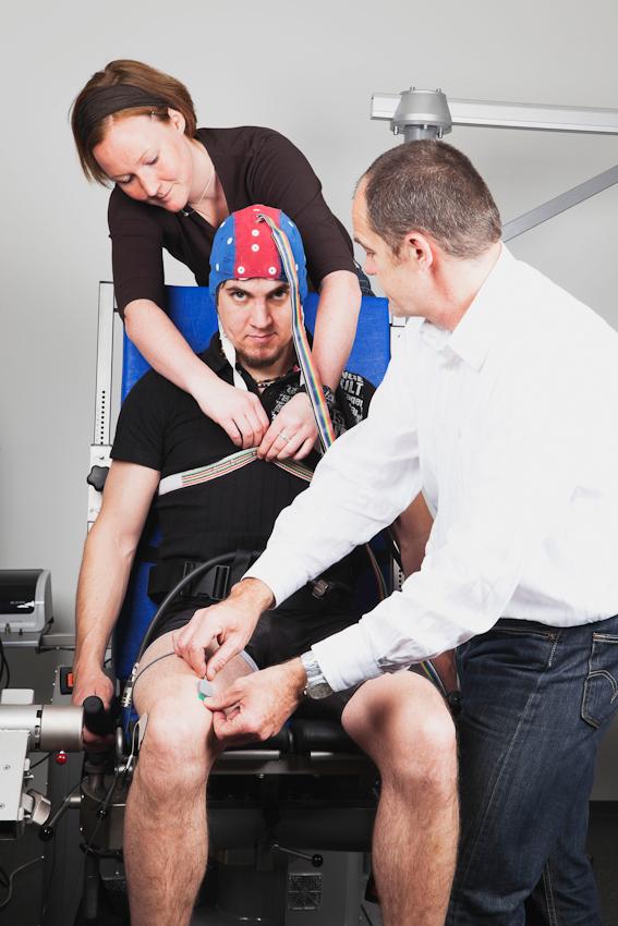 Die Wissenschaftlerin Vera Brummer (links im Hintergrund) und der Laborleiter Dr. Axel Knicker (rechts im Bild) befreien den Probanden Fabian Schurg (Bildmitte) von den Messinstrumenten. Mit Hilfe der Beinelektroden wurde die Muskelaktivität und mit der EEG-Kappe die Gehirnströme gemessen.