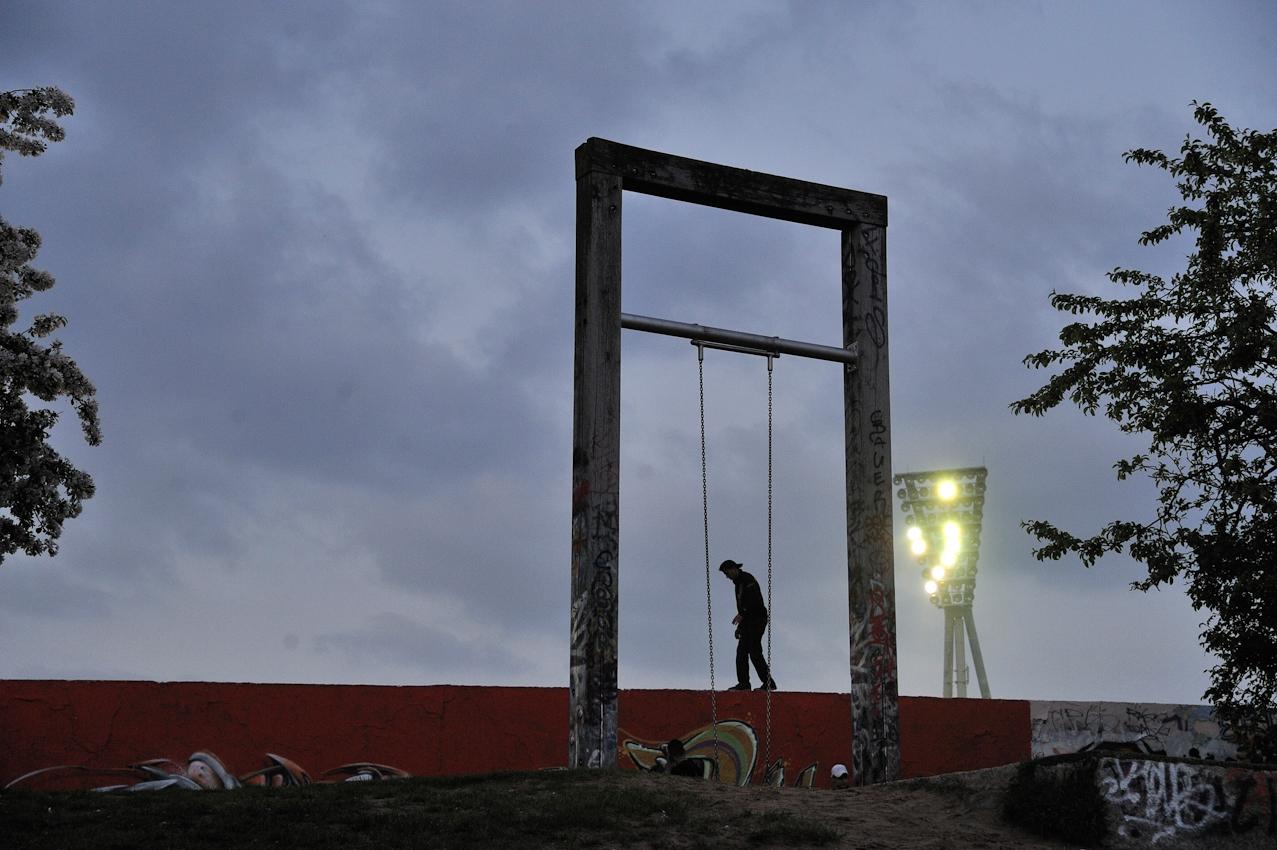 Jugendlicher auf mit Graffiti besprühter inneren Mauer, im Hintergrund Flutlichtmast des Cantian-Stadions.