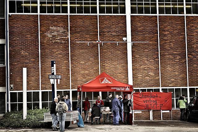 """Stuttgart-Zuffenhausen: Die Beschäftigten der KBA-MetalPrint GmbH, einer hochspezialisierten """"Manufaktur"""" für Blechbedruckmaschinen, kämpfen für ihre Arbeitsplätze, gegen die Schließung des Standorts Zuffenhausen. Bereits entlassene Mitarbeiter halten seit einer Woche vor dem Betrieb Mahnwache unter einem """"Kreuz der Arbeit"""", auf dem die Namen der """"Freigesetzten"""" verzeichnet sind. Sie erhalten Besuch und Solidarität von KollegInnen auch aus den umliegenden Betrieben."""
